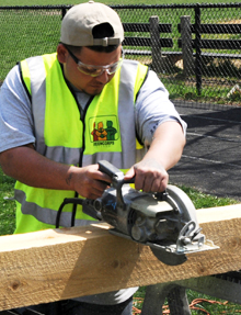 A Greencorps Chicago trainee sawing lumber to build a raised planting bed.